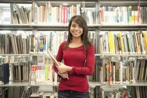 Smiling Hispanic woman holding book in library